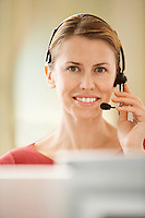 Mid-adult female office worker sitting in cubicle wearing headset portrait