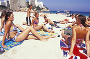 group of teenagers sunbathing on beach, one on union jack towel, Ibiza, 2000's,