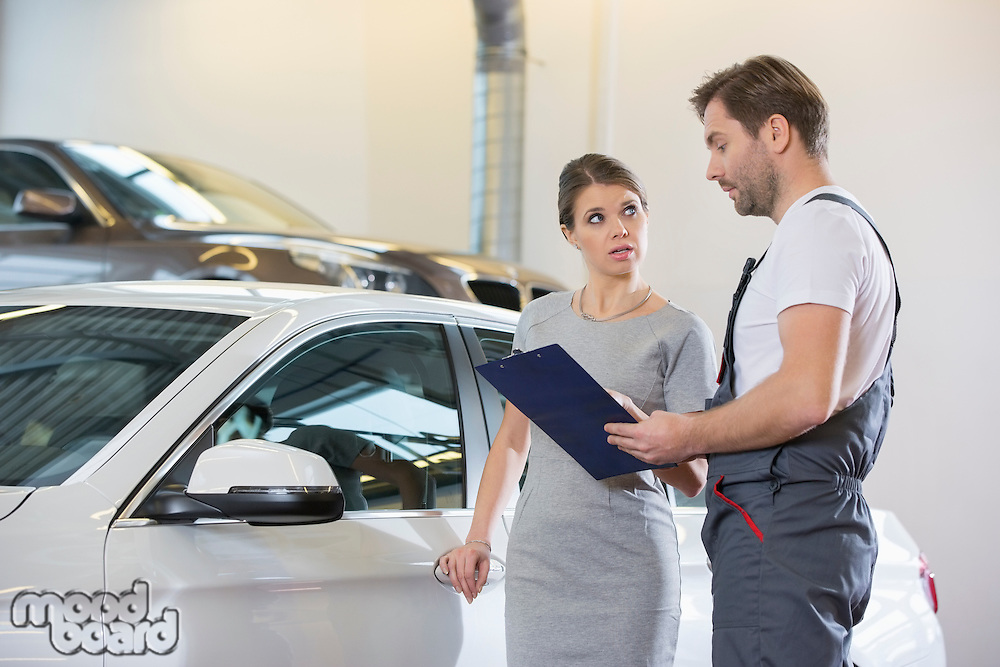 Repairman holding clipboard while conversing with female customer in automobile repair shop