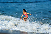Young girl enjoys the ocean water, Cape Cod, Massachusetts, USA.