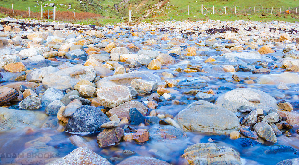 A small temporary stream on Silver Strand Beach at Malin Beg washing over the smoothed pastel coloured rocks.