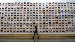 "© Licensed to London News Pictures. 11/11/2019. LONDON, UK. A staff member walks by works at the preview of ""Year 3"", an exhibition by Turner Prize-winning artist and Oscar-winning filmmaker Steve McQueen at Tate Britain.  The artwork comprises 3,128 traditional school class photographs of Year 3 pupils from 1,504 of London's primary schools.  The work reflects a picture of the present and is on display 12 November to 3 May 2020.  Photo credit: Stephen Chung/LNP"
