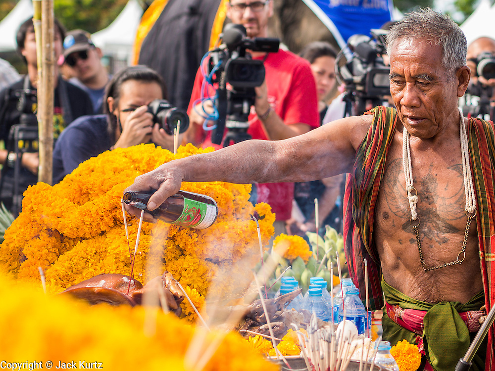 "29 AUGUST 2013 - HUA HIN, PRACHUAP KHIRI KHAN, THAILAND: A ""Khru Ba Yai"" or Elephant Spirit Man, leads a blessing for the elephants before the King's Cup Elephant Polo Tournament in Hua Hin. The tournament's primary sponsor in Anantara Resorts and the tournament is hosted by Anantara Hua Hin. This is the 12th year for the King's Cup Elephant Polo Tournament. The sport of elephant polo started in Nepal in 1982. Proceeds from the King's Cup tournament goes to help rehabilitate elephants rescued from abuse. Each team has three players and three elephants. Matches take place on a pitch (field) 80 meters by 48 meters using standard polo balls. The game is divided into two 7 minute ""chukkas"" or halves. There are 16 teams in this year's tournament, including one team of transgendered ""ladyboys.""    PHOTO BY JACK KURTZ"