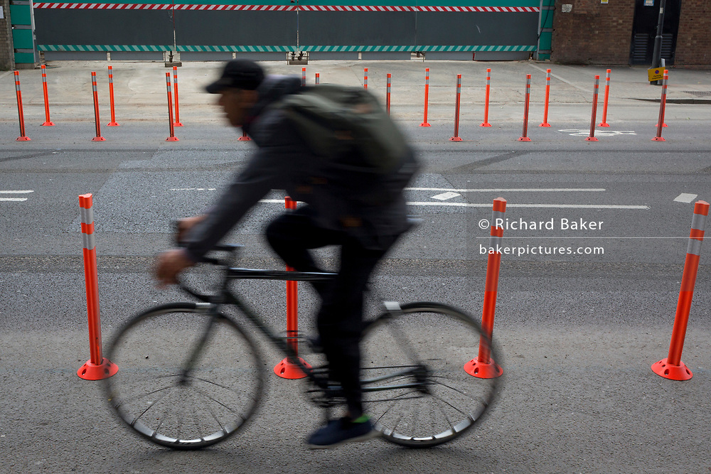 A cyclist speeds past traffic lane bollards in Nine Elms, south London, on 15th June 2019, in London, England.