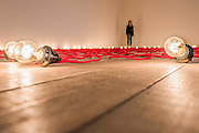 Undercurrent (red) 2008 - Mona Hatoum a new Tate Modern exhibition. It presents around 100 works from the 1980s to the present day, including early performances and video, sculpture, installation, photography and works on paper. Mona Hatoum runs from 4 May to 21 August 2016.<br /> <br /> Highlights include:  Large-scale installations that fill entire rooms, including Impenetrable 2009, a suspended square formed of hundreds of delicate rods of barbed wire which hover above the floor, and Light Sentence 1992, in which walls of wire mesh lockers and a single lightbulb cast constantly moving shadows; Hot Spot 2013, a giant globe that uses red neon to outline the contours of the continents; a kinetic sculpture in which a rotating motor-driven arm draws circular lines across a large sandpit; and Homebound 2000, an installation of kitchen utensils and furniture which buzzes with electricity