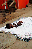 GHANA,Accra,Kokomlemle, 2007. A child is still asleep in the relative cool of morning. Ghanaians sleep outside to take advantage of any available breeze.