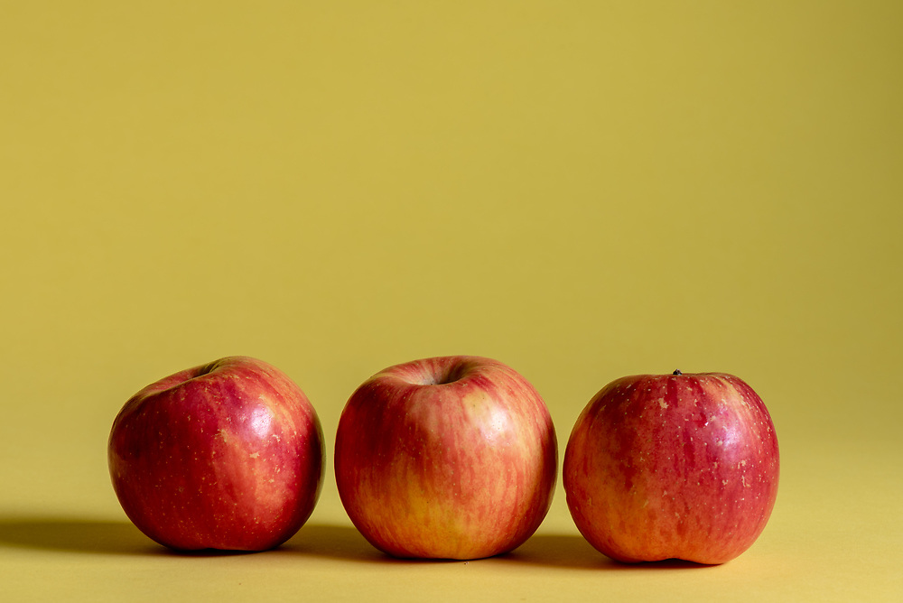 Three red apples on a yellow background.