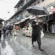 An ultra-orthodox man (R) walks with an umbrella during a rain storm at The Mahane Yehuda Shuk on January 9, 2015 in Jerusalem, Israel. (Photo by Elan Kawesch)