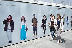 Young Chinese women walking past billboard advertising Weibo microblogging website in Shanghai China