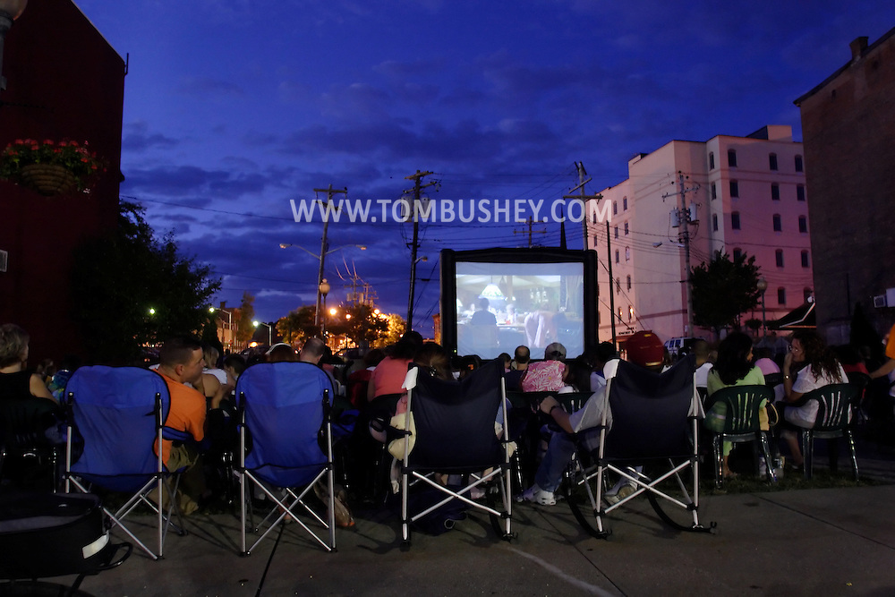 """Middletown, N.Y. - People watch a movie on a portable screen outside at Festival Square on the evening of Aug. 16, 2006. The movie is """"E.T. the Extra-Terrestrial."""" ©Tom Bushey"""