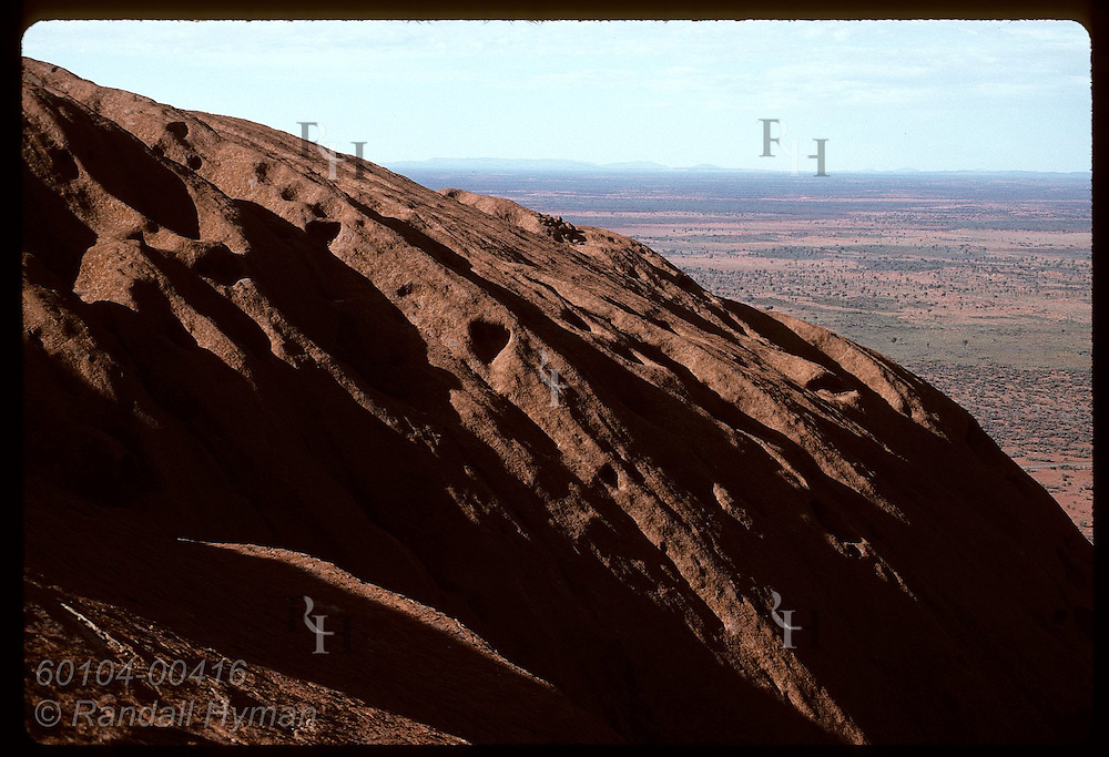 Seen from atop Ayers Rock on a summer morn, sandstone dome arcs against desert horizon; Uluru NP Australia