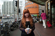 A young woman with bleached red hair and blue nail polish is seen in Shanghai.