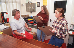Secondary school pupils holding clipboards interviewing teacher,