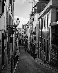 A solitary figure makes their way down a narrow street in Lisbon