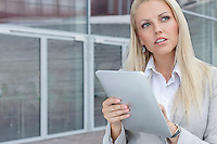 Thoughtful businesswoman using digital tablet while looking away against office building