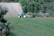 tractor breaking up soil for preparation of plowing the field