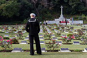 A United States Navy sailor looks at graves of fallen servicemen and servicewomen during the Remembrance Sunday ceremony at the Hodogaya, Commonwealth War Graves Cemetery in Hodogaya, Yokohama, Kanagawa, Japan. Sunday November 11th 2018. The Hodagaya Cemetery holds the remains of more than 1500 servicemen and women, from the Commonwealth but also from Holland and the United States, who died as prisoners of war or during the Allied occupation of Japan. Each year officials from the British and Commonwealth embassies, the British Legion and the British Chamber of Commerce honour the dead at a ceremony in this beautiful cemetery. The year 2018 marks the centenary of the end of the First World War in 1918.