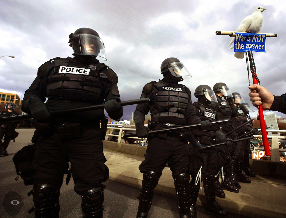 Portland riot police stand their ground as they block the end of the Morrison Bridge from anti-war protesters who had vered off from their designed parade route in an effort to disrupt traffic.