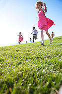 Young kids play in Easter clothing on expansive green lawn in national advertising for Sears spring lifestyle.