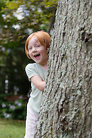 Portrait of girl (3-4) peeking from behind tree laughing