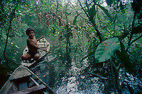 ca. 1986, Near Manaus, Brazil --- mestizo boy canoeing in the Brazilian Amazon --- Image by © Owen Franken