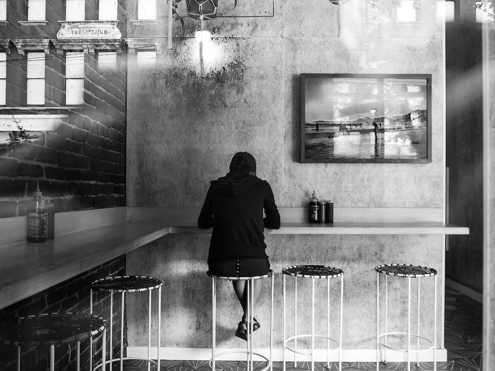 Woman sitting at a bar in a cafe with reflections from the outside.