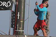 China Team crewman yanks on last spinnaker sheet after afternoon of America's Cup fleet racing; Valencia, Spain.