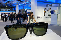 Girl posing beside large exhibit on Olympus stand at Photokina digital imaging trade show in Cologne Germany