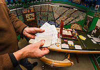 "Bill Colby pulls out the 1971 Baseball season his group is playing with the Strat-O-Matic game in his ""Fenway Park"" room.  (Karen Bobotas/for the Laconia Daily Sun)"