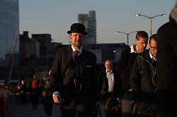 © London News Pictures. 03/04/15. London, UK. A commuter in a bowler hat crosses London Bridge during sunrise, City of London. Photo credit: Laura Lean/LNP