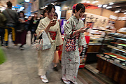 """Blurred young women in kimonos consult smartphones at Nishiki Market in Kyoto, Japan. Nishiki Market is a narrow five-block shopping street lined by 100+ shops and restaurants, in Kyoto, Japan. Known as """"Kyoto's Kitchen"""", this lively retail market specializes in all things food related, like fresh seafood, produce, knives and cookware, and is a great place to find seasonal foods and Kyoto specialties, such as Japanese sweets, pickles, dried seafood and sushi. It all started as a fish wholesale district, with the first shop opening around 1310. The market has many stores that have been operated by the same families for generations. Nishiki Ichiba often gets tightly packed with locals and visitors."""