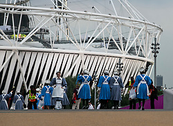 © Licensed to London News Pictures.27/07/2012 LONDON UK. Cast memebers dressed as nurses make there way to the stadium..London2012 Olympic Stadium, during the opening Ceremony of the London 2012 Olympic Games. Photo credit : Andrew Baker/LNP