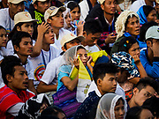 29 NOVEMBER 2017 - YANGON, MYANMAR: A woman holding a Vatican flag appears to be sleeping before the Pope's arrival at the Papal Mass in Yangon. Hundreds of thousands of Catholics from Myanmar attended the mass said by Pope Francis at Kyaikkasan Sports Ground in Yangon Wednesday. Pope Francis is on the first visit by a Pope to Myanmar.   PHOTO BY JACK KURTZ