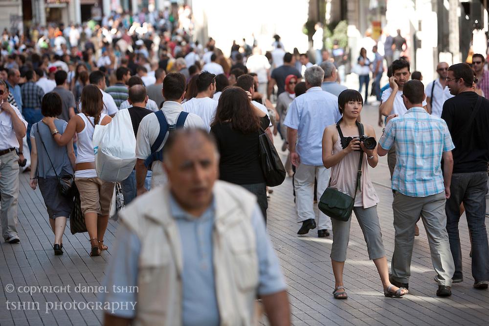 Pedestrians walking along ?stiklal Avenue, a walking street, in Beyo?lu on a summer afternoon.