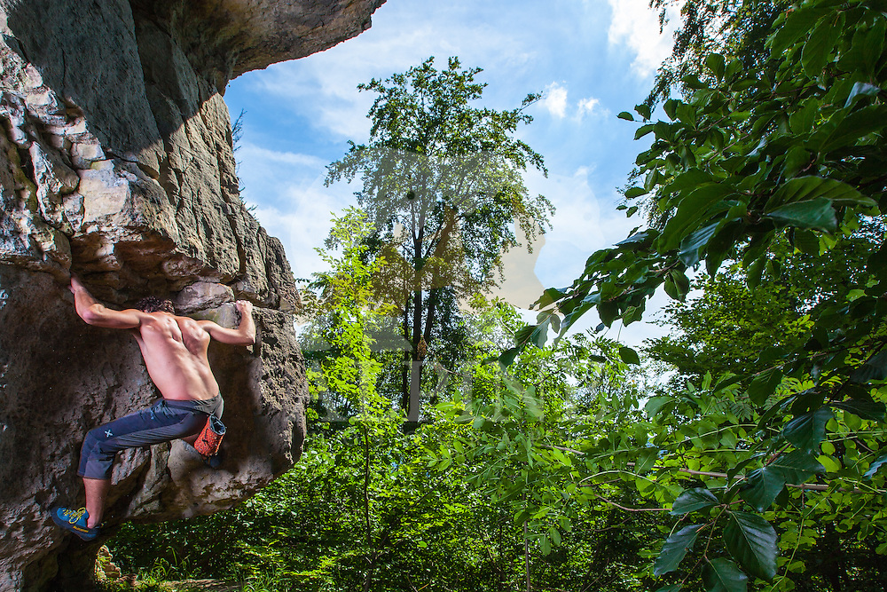 Antonio Caretta, a talented Italian climber, opens a difficult and exposed bouldering project, which starts with an overhanging and protruding rock feature deep in the forests of Hameln, Lower Saxony, Germany on June 3 2011.