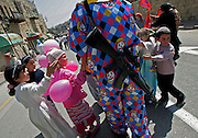 Young Israeli settler children gather around an elder dressed as a clown armed with an M-16 rifile in the divided West Bank city of Hebron during Purim celebrations March 27,2005. Palestinians living in the area of the Jewish settlements in Hebron were places under curfew so that the Jews could carry out their annual Purim parade celebrations. (Photo by Heidi Levine/Sipa Press).