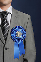 Man wearing blue ribbon on lapel against dark background mid section
