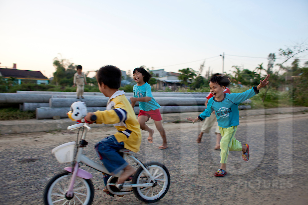 3 kids are running and playing after a bicycle in a street near Hoi An, Vietnam, Asia