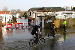 © Licensed to London News Pictures. 06/01/2014, Christchurch, UK. Cyclists ride pass a flooded road at Iford Bridge, Christchurch, England , Monday, Jan. 6, 2014. Part of UK continue to be affected by floods and strong wind. Photo credit : Sang Tan/LNP