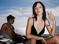 Woman holding champagne glass man relaxing near sea