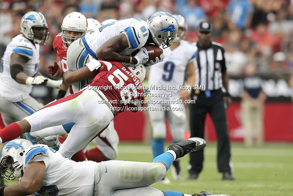 15 SEPT 2013: Cardinals Karlos Dansby (56) tackles Lions' widereceiver Calvin Johnson (81) in mid-air during the Arizona Cardinals hosting the Detroit Lions at the University of Phoenix Stadium in Glendale, AZ.