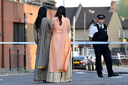 © Licensed to London News Pictures. 06/05/2018. LONDON, UK. Passers by view the police cordon off Palmerston Road in Wealdstone, near Harrow, north west London, following reports of two separate shooting incident around midday on Sunday 6 May 2018.  The two victims are a 12 year old boy and a15 year old boy.  Investigations are ongoing.  Photo credit: Stephen Chung/LNP