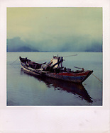 Polaroid of a single old row boat moored near shore surrounded by the calm waters of Halong Bay, Quang Ninh Province, Vietnam, Southeast Asia. Odd objects are seen piled inside the boat and the Karstic landscape is hidden by the mist in the background.