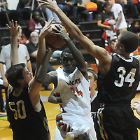 New Hanover's Acchaeus Fields drives through Ashley's Ryan Keller, left, and Bryston Davis Friday December 19, 2014 at New Hanover High School in Wilmington, N.C. (Jason A. Frizzelle)