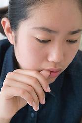 Teenage girl doing her homework; looking thoughtful,