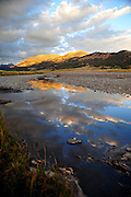 Evening clouds reflected in still water of Soda Butte Creek, Yellowstone.