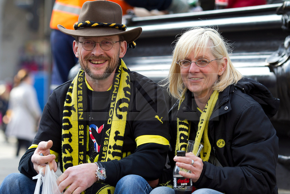 © Licensed to London News Pictures. 25/05/2013. London, UK. Two Borussia Dortmund fans sit on the base of the statue of Eros in Piccadilly Circus, London, today (25/05/2013) as fans of Borussia Dortmund and Bayern Munich celebrate before their teams meet in the first ever all German Champions League final tonight. Photo credit: Matt Cetti-Roberts/LNP