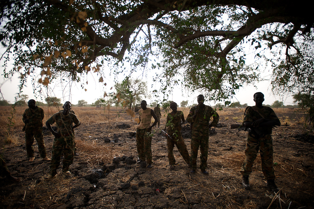 April 24, 2012 - Panakuach, South Sudan: A group of SPLA soldiers rest under a tree in the last defensive line outside the village of Panakuach, 70 kilometers north of Bentiu...South Sudan and their northern neighbors, Sudan, have in the past two weeks been involved in heavily clashes over border disputes. Bentiu and neighboring villages have been under constant bombardment by the troops os Karthoum , who established their positions around 10 kilometers into South Sudan's territory. The international community is concerned about the possibility of a full on war between the two countries. (Paulo Nunes dos Santos/Polaris)