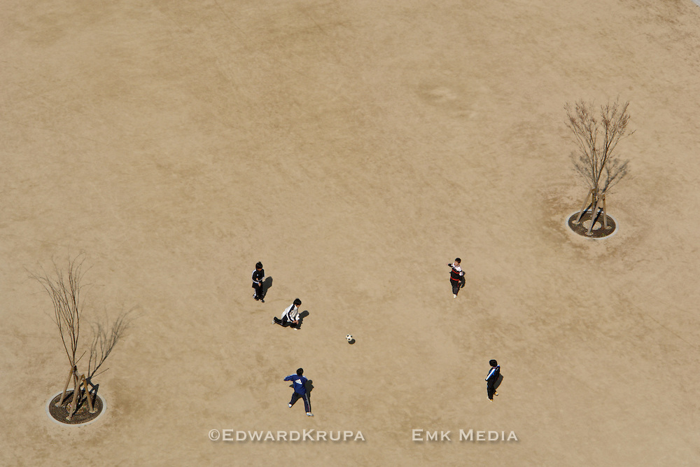 Arieal view of a group of young boys kicking around a football in a large grassless field in Tokyo.