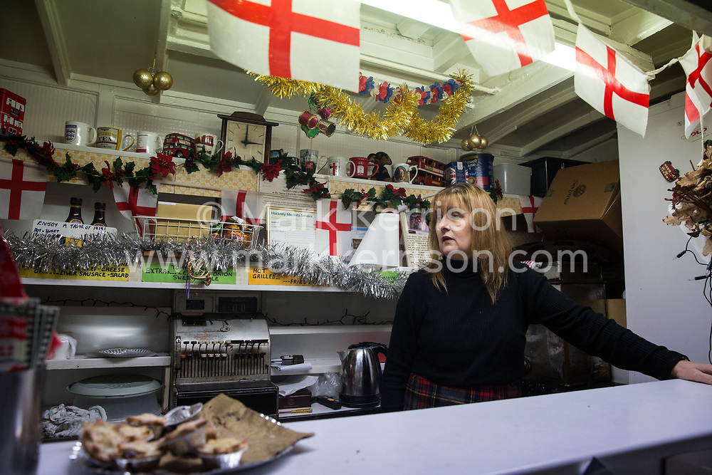 London, UK. 20 December, 2019. Cheryl Diamond prepares to close Syd's Coffee Stall, which has been run by three generations of the same family on the corner of Shoreditch High Street and Calvert Avenue since 1919. The mahogany coffee stall, part of east London's history, will go on display in the new Museum of London in Smithfield in 2024.